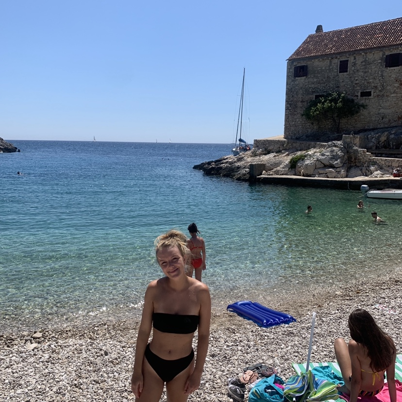 A woman in front of a beach at Dubovika, one of the things to do in Hvar.