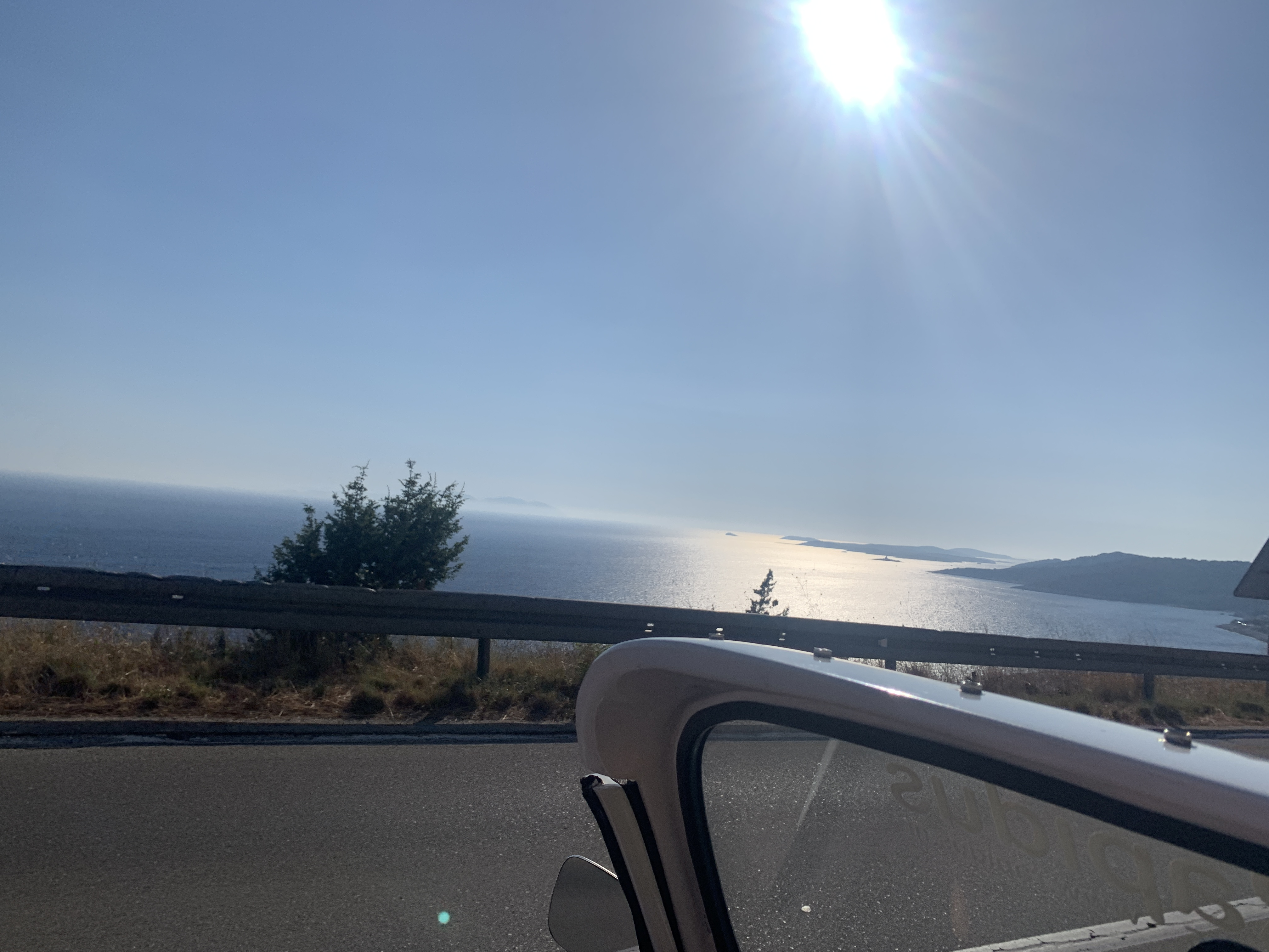 The sun glistening on the ocean, being seen from a car.