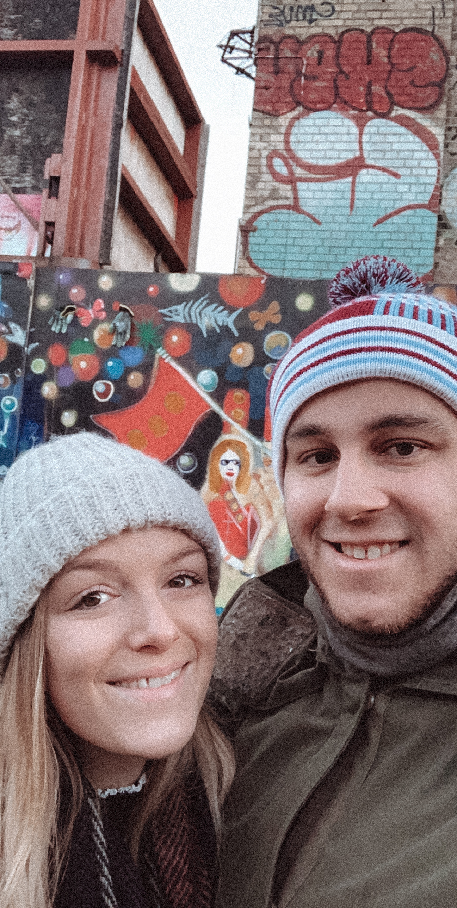 Two people having a selfie in front of graffiti.