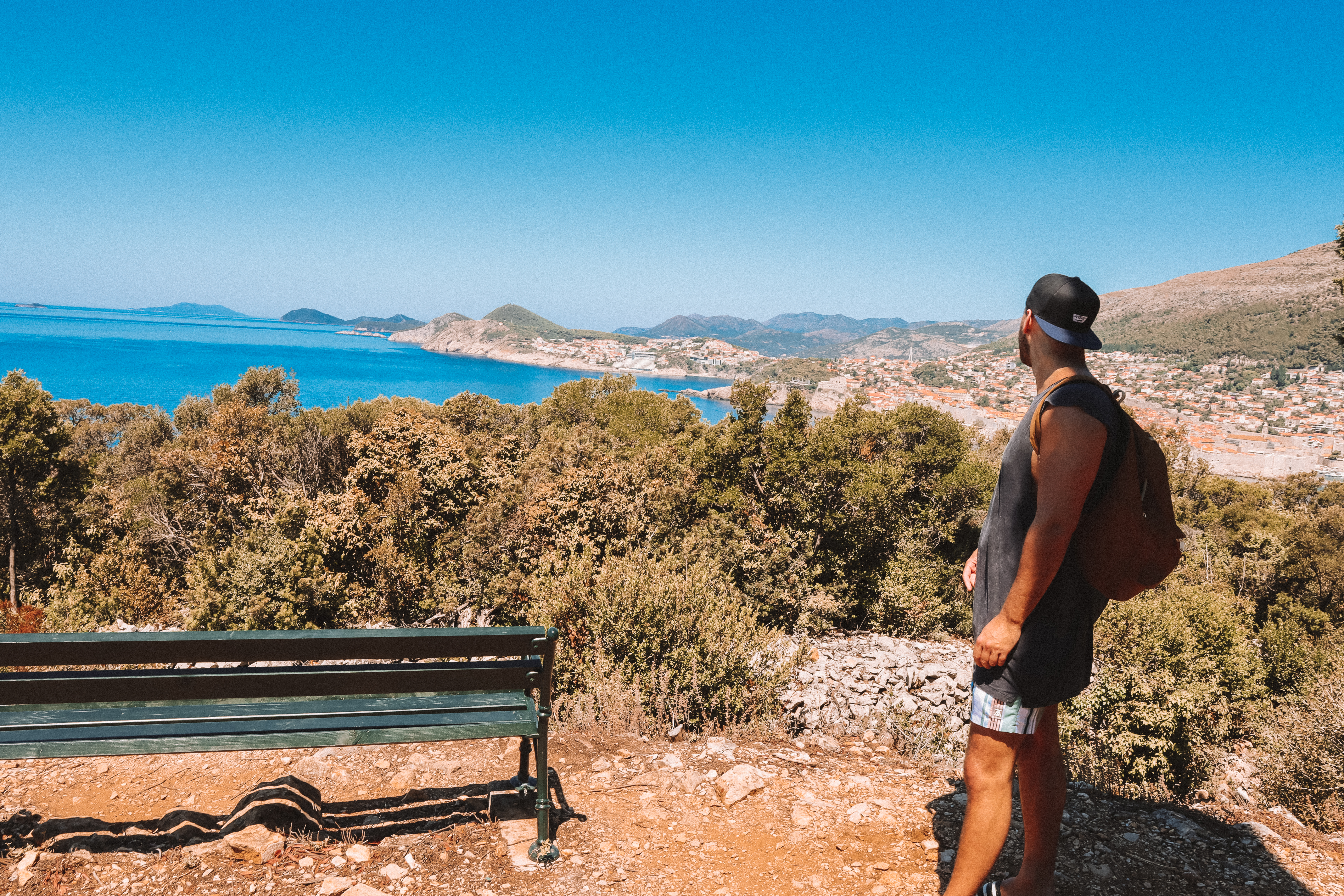 A man looking at the ocean and old town in the background in Dubrovnik. Things to do in Dubrovnik.