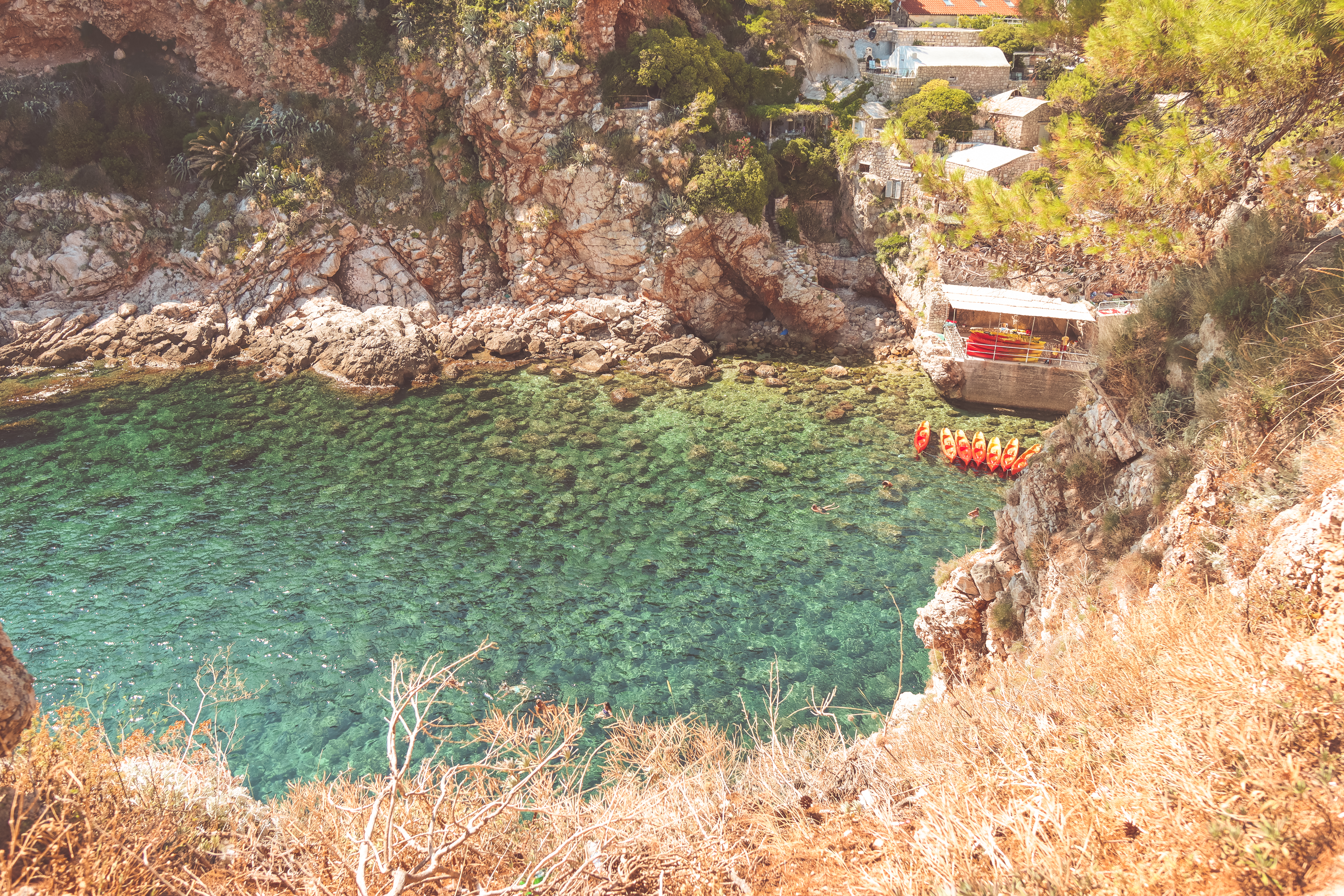 Turquoise ocean with orange and yellow kayaks in them. Things to do in Dubrovnik